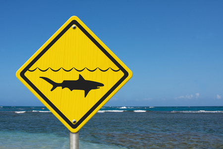 Yellow Warning Sign with symbol of shark and water with ocean background