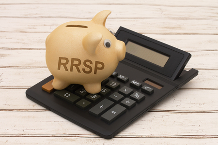 canadian coin: A golden piggy bank and calculator on a wood background with text RRSP