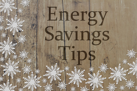 saving tips: White Snowflakes on Weathered Wood Background and text Energy Savings Tips Stock Photo