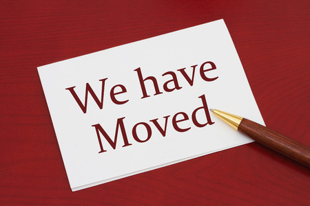 we have moved: White Greeting card with text We have Moved on a red wood background