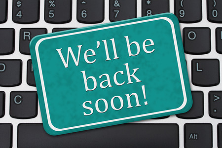 A teal and white sign with the words Well Be Back Soon on a computer keyboard