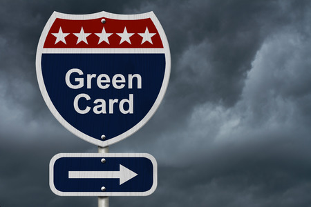 Blue, Red and White highway sign with words Green Card with stormy sky background