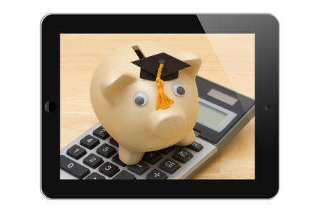grad: Piggy bank with grad cap on a calculator on a tablet display Stock Photo