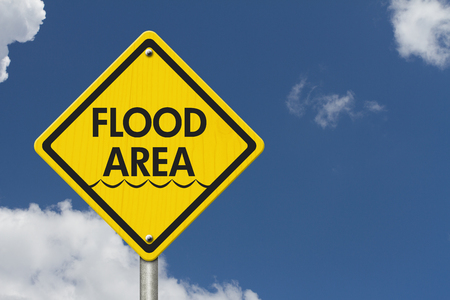 flood area: Yellow Warning Highway Sign with words Flood Area with sky background