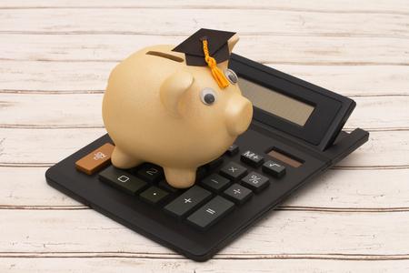 Costo de la educación, una hucha de oro con el casquillo del graduado y la calculadora en un fondo de madera