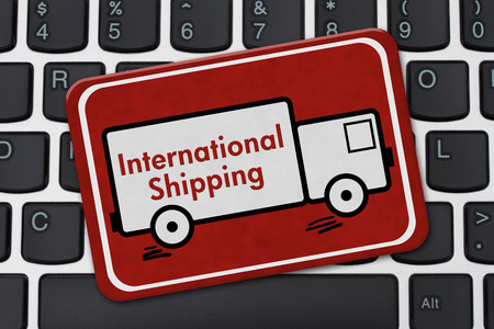 international shipping: International Shipping Sign, A red hanging sign with text International Shipping on a truck on a keyboard Stock Photo