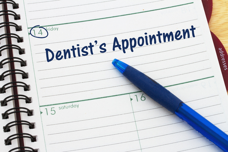 schedulers: Scheduling your dentists appointment, a day planner with blue pen with text Dentists Appointment