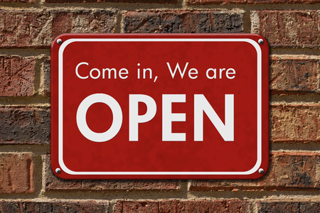 come in: Come in We are Open Sign, A red hanging sign with text Come in We are Open on a brick wall