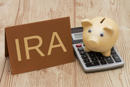 Having a IRA plan, A golden piggy bank, card and calculator on wood background with text IRA Stock Photo - 55438589