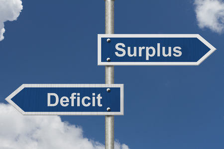 deficit: Difference between a Surplus and a Deficit, Two Blue Road Sign with text Surplus and Deficit with sky background
