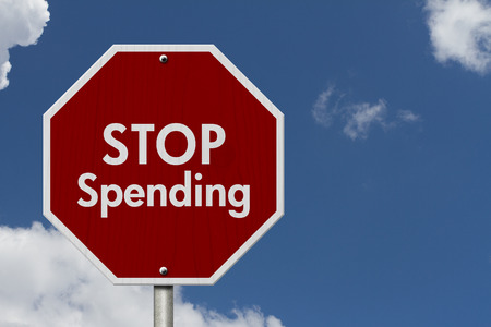 spending: Stop Spending Road Sign, Red and White Stop Sign with words Stop Spending with sky background