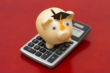cost of education: Cost of education, A golden piggy bank with grad cap and calculator on a wood background