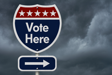 American Vote Here Highway Road Sign, Red, White and Blue American Highway Sign with words Vote Here with stormy sky background Stock Photo