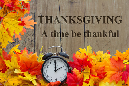 A time to be Thankful, Autumn Leaves and Alarm Clock with grunge wood with text Thanksgiving a time be thankful