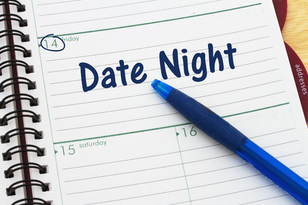date night: Planning your Date Night, A pen and a day planer with text Date Night Stock Photo