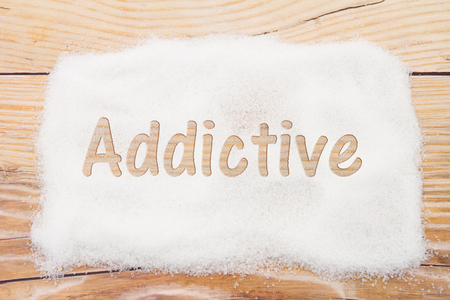 Close-up of sugar with text Addictive on weathered wood background Imagens