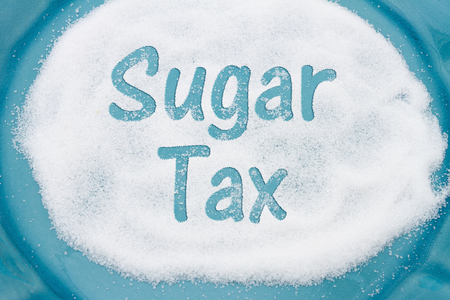 Close-up of Teal Plate with a lot of sugar with text Sales Tax