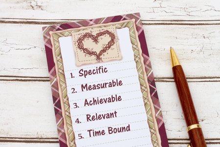 measurable: Writing your SMART Goals, A notepad and pen on weathered wood background with text listing SMART Goals Stock Photo