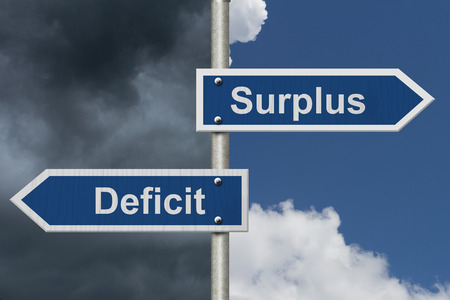 deficit: Difference between a Surplus and a Deficit, Two Blue Road Sign with text Surplus and Deficit with bright and stormy sky background Stock Photo