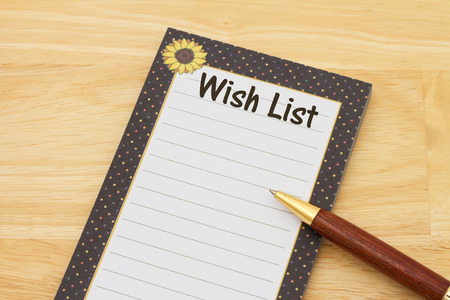 wishlist: Blank wish list of notepad and paper, A notepad and pen on a desk with text Wish List and copy-space Stock Photo