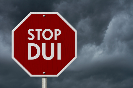 dui: DUI Stop Road Sign, Red and White Stop Sign with words Stop DUI with stormy sky background