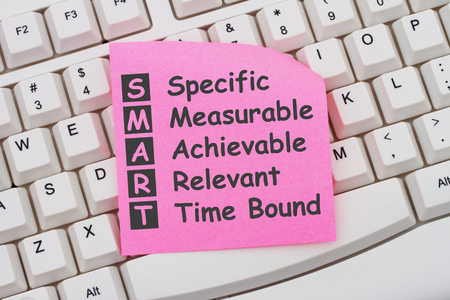 computers online: Writing your SMART Goals, Computer Keyboard with a pink sticky note with text listing SMART Goals Stock Photo