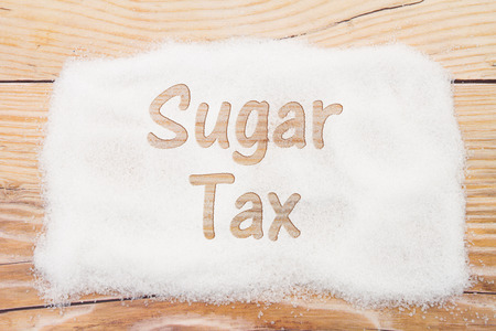 Close-up of sugar with text Sales Tax on weathered wood background