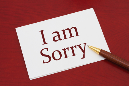 regretful: I am Sorry Card, White Greeting card with text I am Sorry on a red wood background Stock Photo