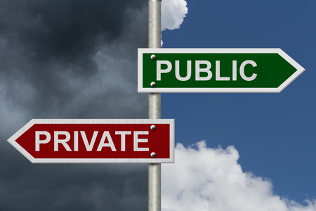 private schools: Public versus Private concept, Red and Green street signs with blue and stormy sky with words Public versus Private Stock Photo