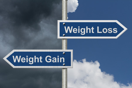wort: Gewichtsverlust im Vergleich zu Gewichtszunahme, Zwei blaue Straßenschild mit Text Gewichtsverlust und Gewichtszunahme mit hellen und stürmischen Himmel Hintergrund Lizenzfreie Bilder