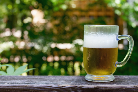rallying: Cold beer on a warm summers day, A beer of mug on a deck rallying with tree background