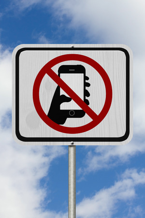 txt: No Texting Road Sign,  A white Road Sign with symbol of hand and mobile phone with sky background Stock Photo