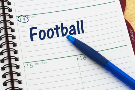 Friday night football schedule, a day planner with blue pen with text Football