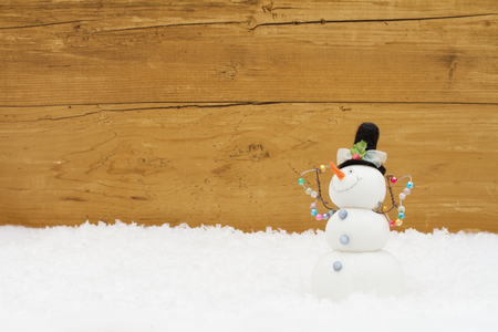 snowman wood: Happy Holidays, A Snowman on snow with a weathered wood background and copy-space for your message