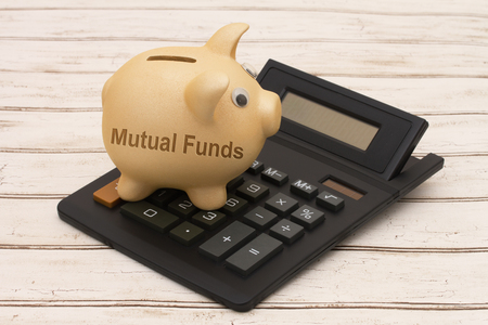 mutual: Mutual Funds Savings, A golden piggy bank and calculator on a wood background with text Mutual Funds Stock Photo