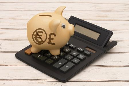 banco dinero: El uso de la moneda libra en lugar del Euro, Una hucha de oro y una calculadora en un fondo de madera con el símbolo de la libra y el euro