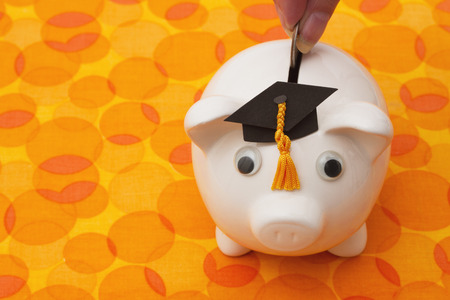 grad: Saving Money for Education, A white piggy bank with grad hat on orange circle background Stock Photo