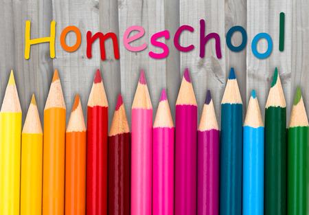 Potloodkleurpotloden met tekst Homeschool met verweerde houten achtergrond Stockfoto