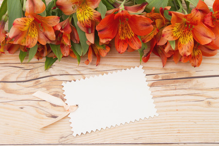 blank tag: Some lilies on weathered wood with a blank Gift Tag and copy space for your message