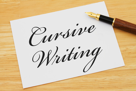 cursive: Learning how to write cursive, White Greeting card with text Cursive Writing on a wood background