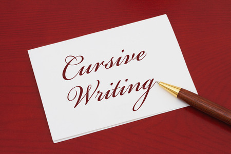 cursive: Learning how to write cursive, White Greeting card with text Cursive Writing on a red wood background