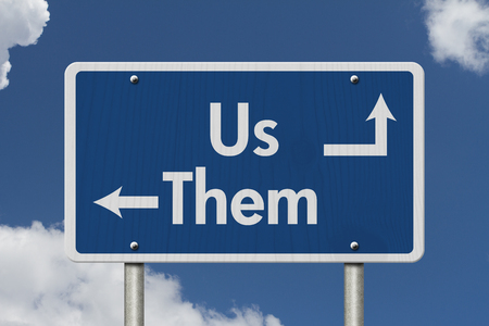 them: Difference between the Us and the Them, Blue Road Sign with text Us and Them with sky background Stock Photo