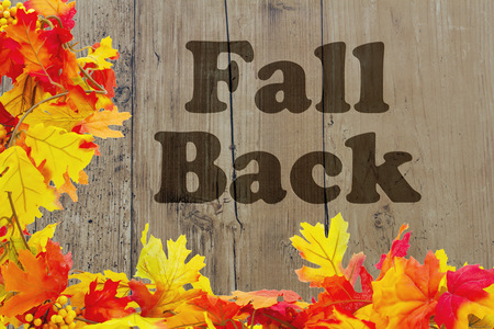Fall Back Time Change, Autumn Leaves with grunge wood and words Fall Back Stock Photo