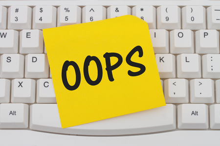 computers online: Having problems with your computer, A close-up of a keyboard with yellow sticky note with text Oops