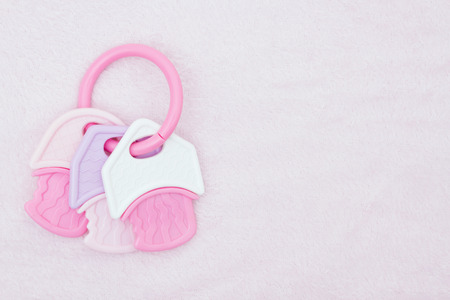 teething: Baby Girl Background, A pink and white teething ring on pink fluffy material with copy space for your message