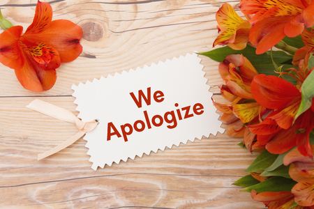 We Apologize Message, Some lilies on weathered wood with We Apologize Gift Card and copy space for your message Banque d'images