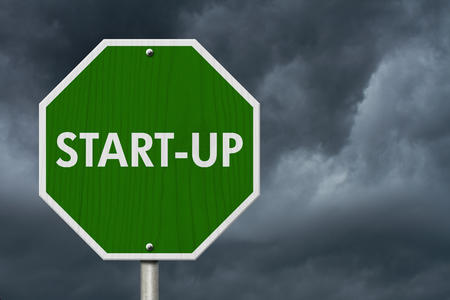 selfemployed: Green Start-up highway road sign, Green stop highway sign with words Start-up with stormy sky background