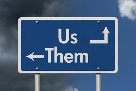 them: Difference between the Us and the Them, Blue Road Sign with text Us and Them with bright and stormy sky background Stock Photo