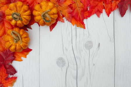 space wood: fall leaves and pumpkins on weathered wood with copy space for message Stock Photo