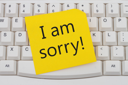 i am sorry: A close-up of a keyboard with yellow sticky note with text I am Sorry Stock Photo